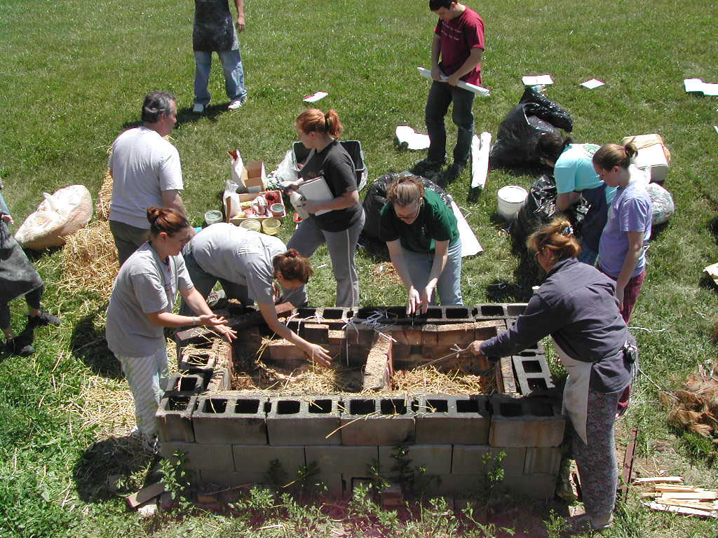 Students loading the pit for a pit firing